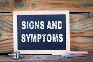 signs and symptoms. Chalkboard on a wooden background.